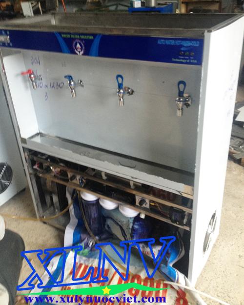 Nhân viên kỹ thuật đang test máy nước uống nóng lạnh trước khi đưa đến công trình lắp đặt